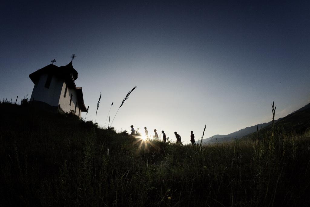 Kids walk towards the orthodox church in Valea Screzii at sunset